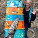 Artist standing behind lighthouse sculpture