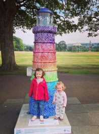 Two children standing in front of colourful model lighthouse